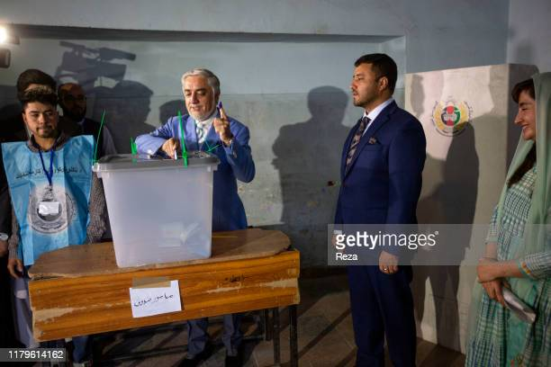 On the voting day, the candidate Dr Abdullah conducts his civil duty by voting under the watch of the staff and Farkhunda Zahra Naderi, member of his...