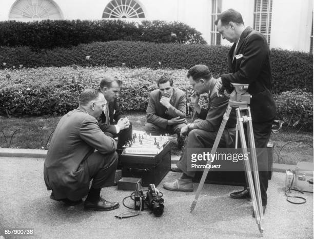 On the White House driveway members of the White House press corps play a game of chess on an equipment case during a break Washington DC April 21...