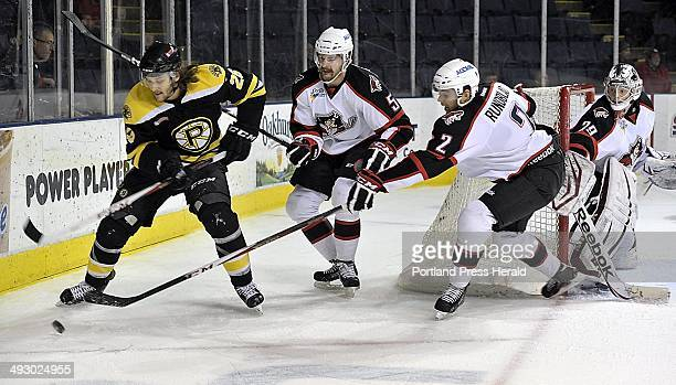 On Wednesday January 2 Bruins Christian Hanson Pirates Chris Summers and David Rundblad battle for control behind the Pirates goal while goalie #29...