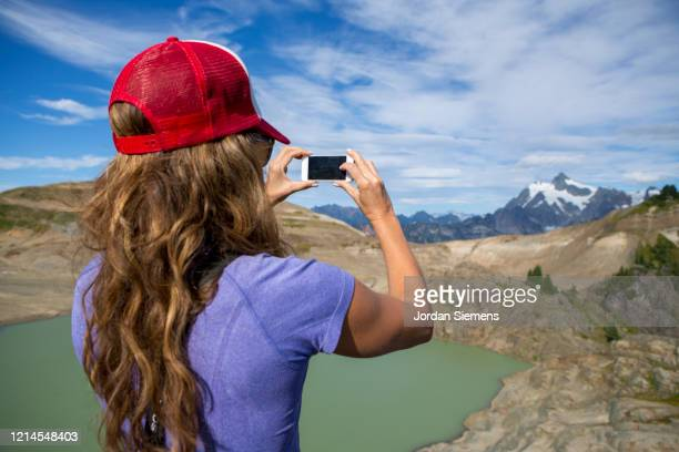 on woman using her phone to shoot photos in the mountains. - bellingham stock pictures, royalty-free photos & images