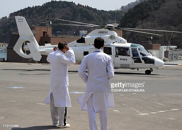 Onagawa town hospital doctors watch a helicopter landing beside the hospital in Onagawa town Miyagi prefecture on April 14 2011 Japan's seismologists...