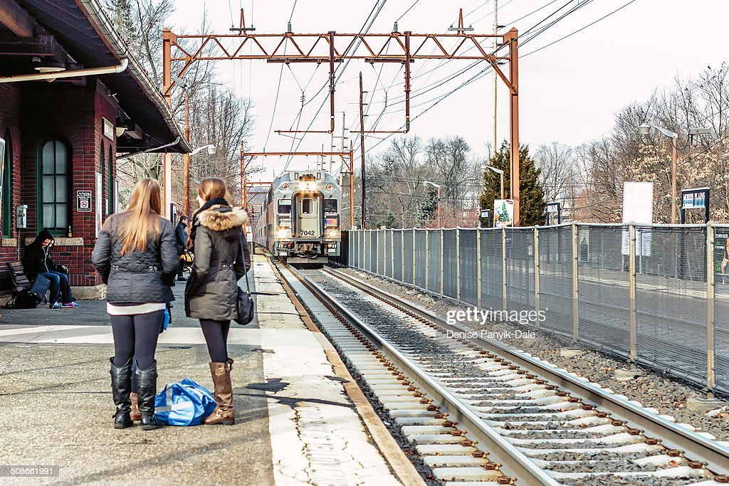 Oncoming eastbound train to New York Penn Station entering Morris Plains (New Jersey) train station as commuters wait.