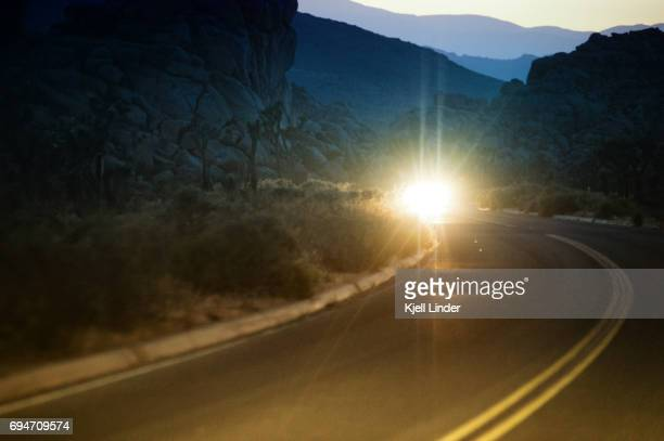 Oncoming headlights from a car on desert road