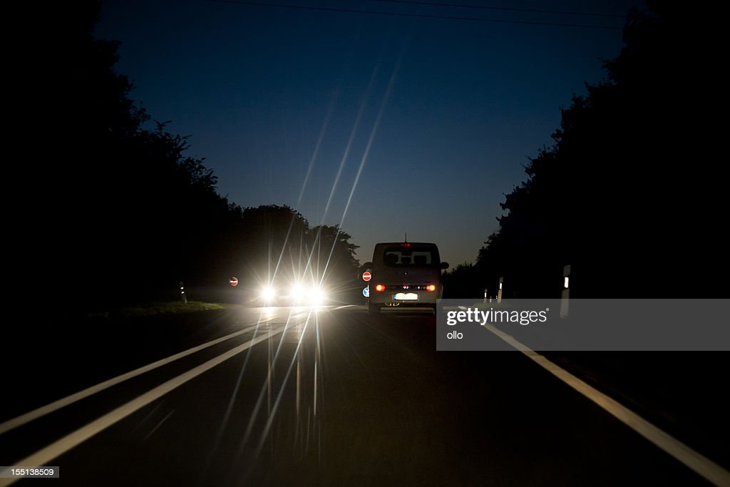 Oncoming traffic on countryroad at dusk : Stock Photo