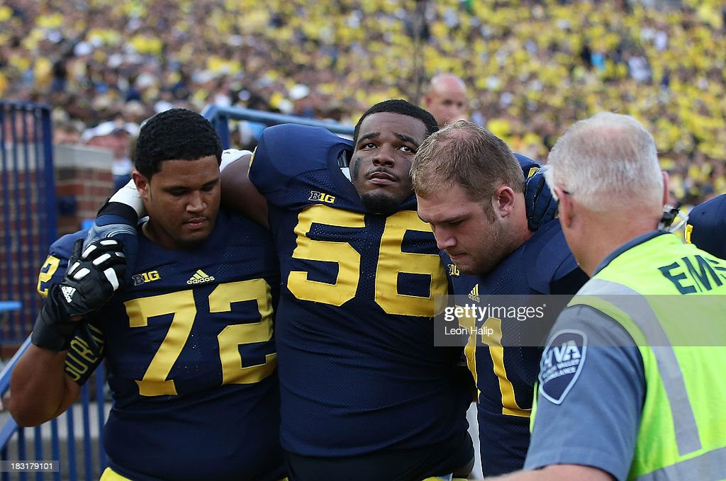 Ondre Pipkins #56 of the Michigan Wolverines is helped onto the cart by teammates Logan Tuley-Tilman #72 and Ben Braden #71 after an injury during the game against the Minnesota Golden Gophers at Michigan Stadium on October 5, 2013 in Ann Arbor, Michigan. Michigan defeated Minnesota 42-13.