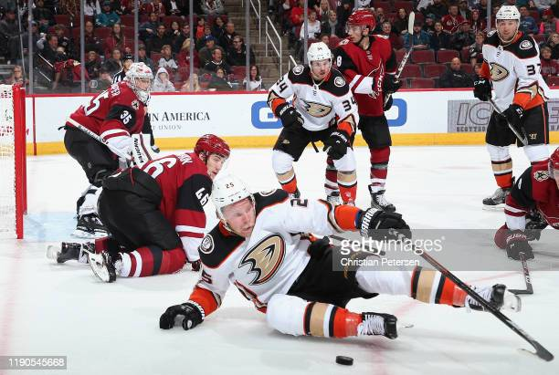 Ondrej Kase of the Anaheim Ducks attempts to control the puck ahead of Ilya Lyubushkin and goaltender Darcy Kuemper of the Arizona Coyotes during the...
