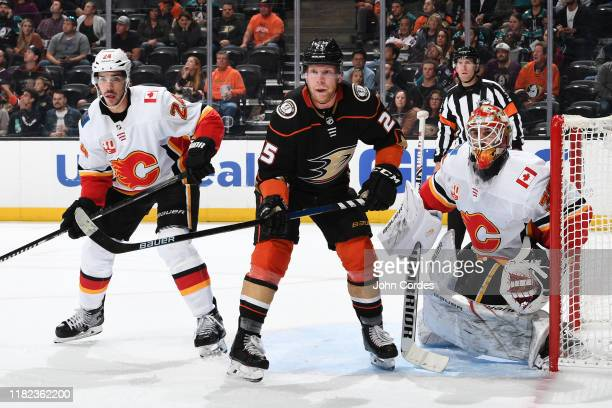 Ondrej Kase of the Anaheim Ducks battles for position against Travis Hamonic and Cam Talbot of the Calgary Flames during the game at Honda Center on...