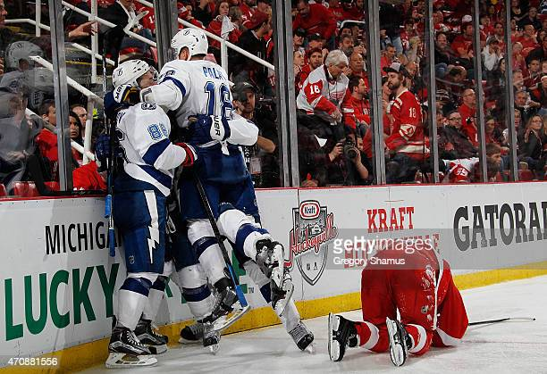 Ondrej Palat of the Tampa Bay Lightning celebrates with Nikita Kucherov next to Darren Helm of the Detroit Red Wings after a overtime game winning...