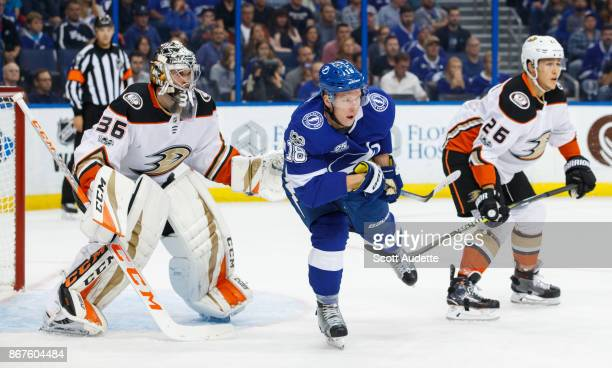Ondrej Palat of the Tampa Bay Lightning has his leg hooked by Brandon Montour of the Anaheim Ducks and in front of goalie John Gibson during the...
