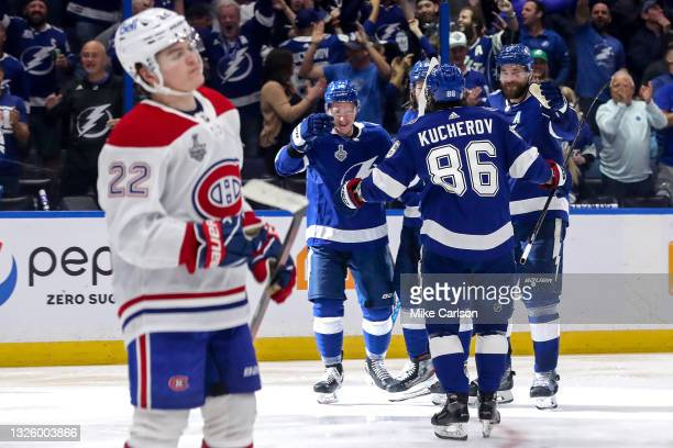 Ondrej Palat of the Tampa Bay Lightning is congratulated by his teammates after scoring a goal against the Montreal Canadiens as Cole Caufield reacts...