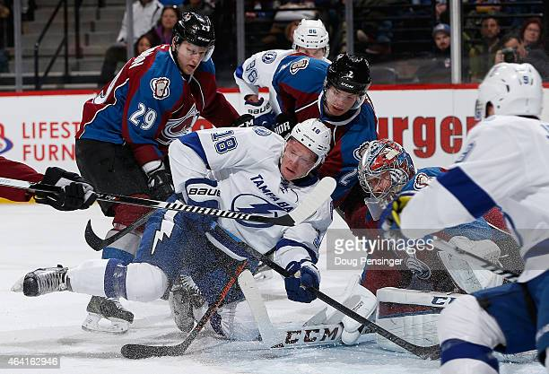 Ondrej Palat of the Tampa Bay Lightning tries to control the puck against Nathan MacKinnon and Nick Holden of the Colorado Avalanche as goalie Semyon...