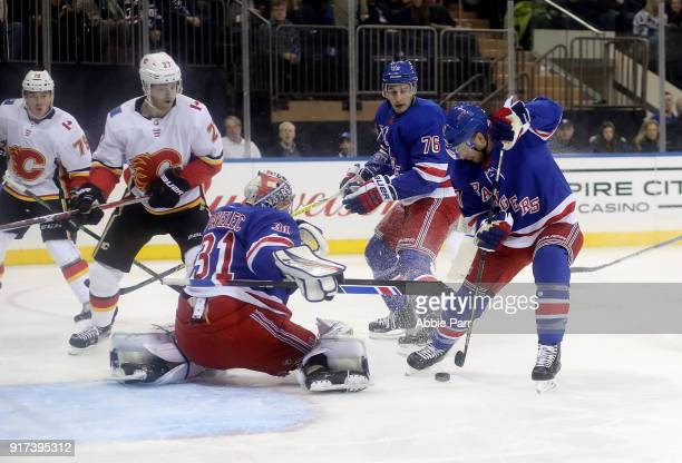 Ondrej Pavelec and Steven Kampfer of the New York Rangers defend the goal against the Calgary Flames during their game at Madison Square Garden on...