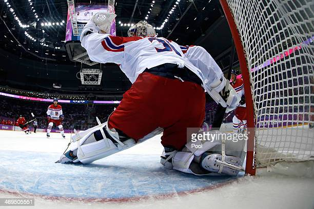 Ondrej Pavelec of the Czech Republic gives up a goal to Simon Bodenmann of Switzerland in the first period during the Men's Ice Hockey Preliminary...