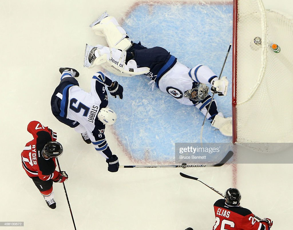 Ondrej Pavelec #31 of the Winnipeg Jets blocks the net against Patrik Elias #26 of the New Jersey Devils at the Prudential Center on October 30, 2014 in Newark, New Jersey. The Devils defeated the Jets 2-1 in the shootout.