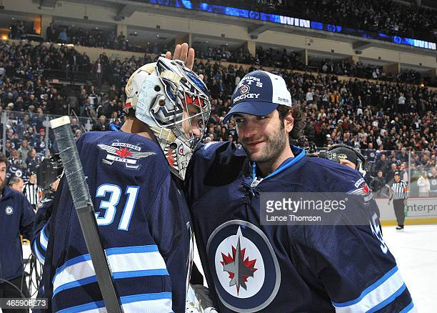 Ondrej Pavelec of the Winnipeg Jets gets congratulated by teammate Al Montoya after backstopping the Jets to a 51 victory over the Phoenix Coyotes at...