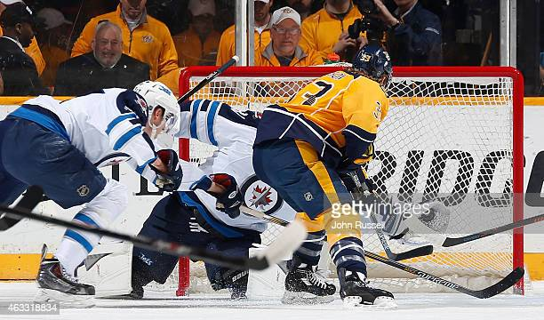 Ondrej Pavelec of the Winnipeg Jets gloves the shot of Colin Wilson of the Nashville Predators during an NHL game at Bridgestone Arena on February 12...