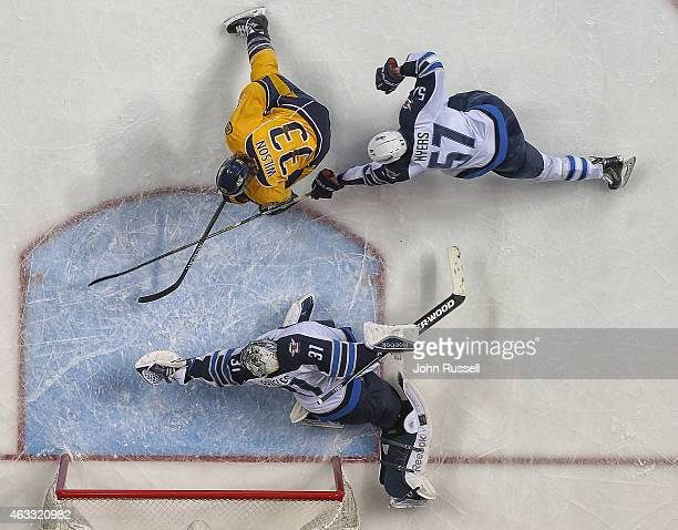 Ondrej Pavelec of the Winnipeg Jets makes a glove save against Colin Wilson of the Nashville Predators as Jets Tyler Myers defends during an NHL game...