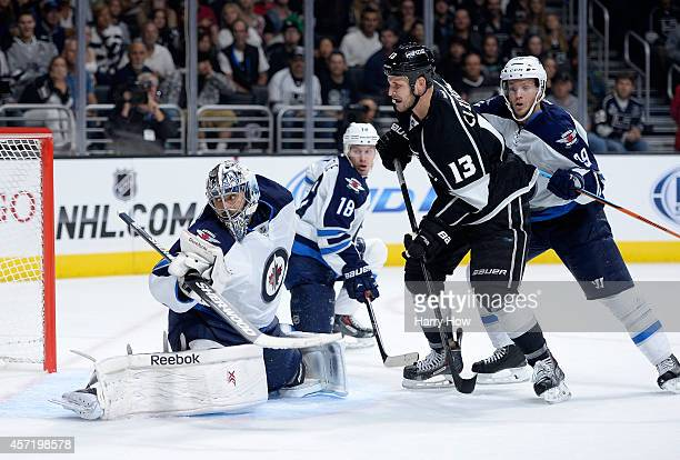 Ondrej Pavelec of the Winnipeg Jets makes a save in front of Kyle Clifford of the Los Angeles Kings as Bryan Little and Tobias Enstrom look for a...