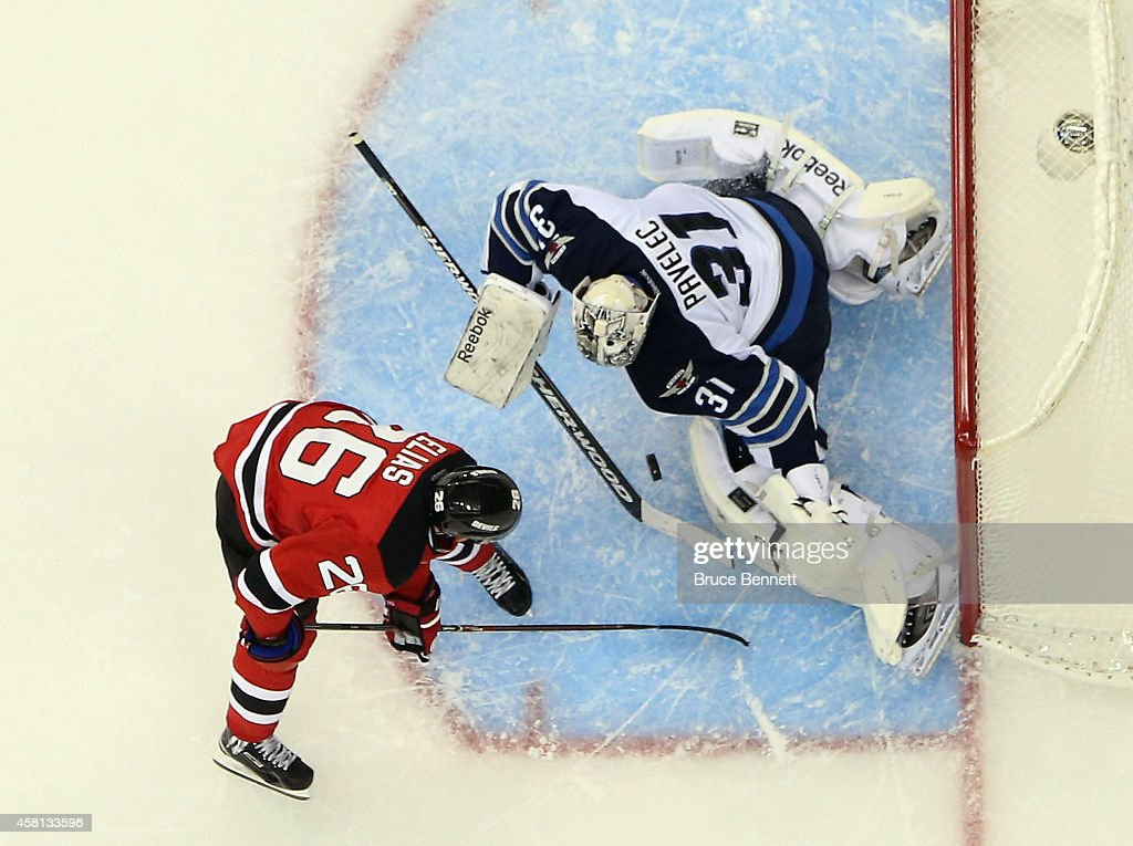 Ondrej Pavelec #31 of the Winnipeg Jets makes the save in the shootout against Patrik Elias #26 of the New Jersey Devils at the Prudential Center on October 30, 2014 in Newark, New Jersey. The Devils defeated the Jets 2-1 in the shootout.