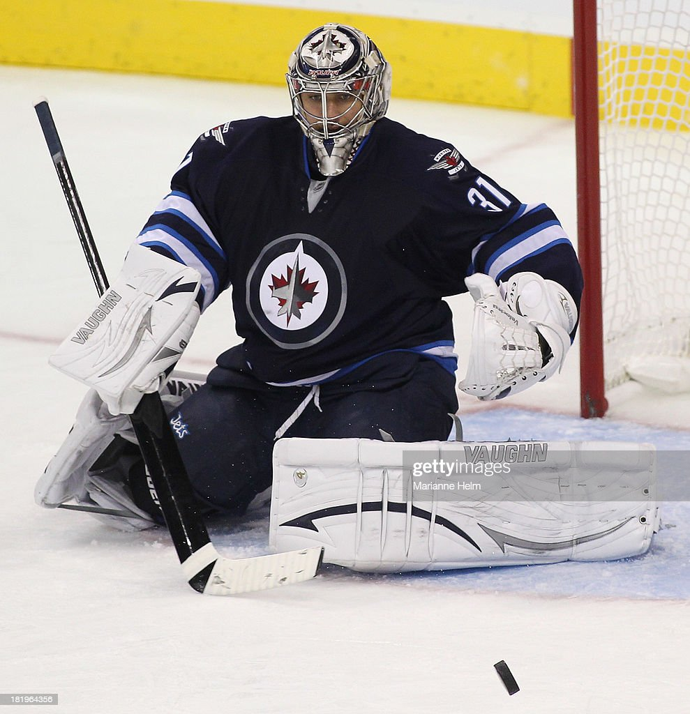 Ondrej Pavelev #31 of the Winnipeg Jets deflects a shot on goal in third period action during an NHL preseason game against the Boston Bruins at the MTS Centre on September 26, 2013 in Winnipeg, Manitoba, Canada.