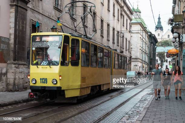 onductor man standing by trolley tram in historic ukrainian polish city in old town with crowd of people, rail tracks, wires coffee cafe shops, restaurants during day - ukraine stock pictures, royalty-free photos & images