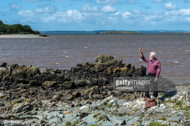 one active senior man at the coast on a sunny and windy day waving - johnfscott stock pictures, royalty-free photos & images