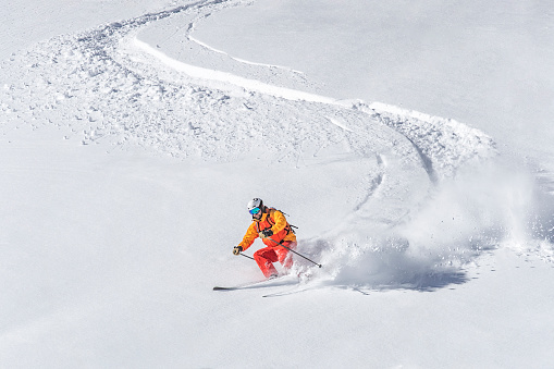 One adult freeride skier skiing downhill through deep powder snow 1082876840