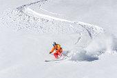 One adult freeride skier skiing downhill through deep powder snow