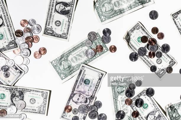 one and five dollar bills and coins on white background - geld und finanzen stock-fotos und bilder