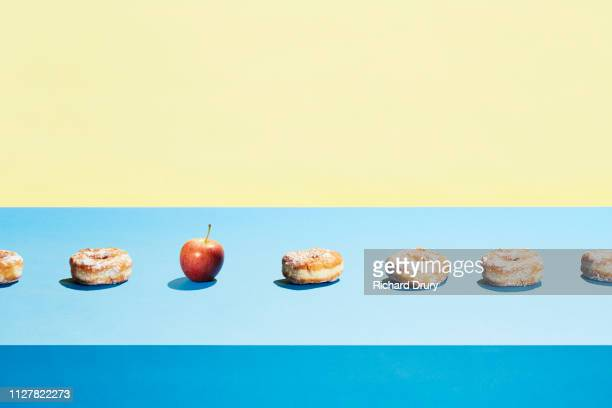 one apple in a row of donuts - decisions imagens e fotografias de stock