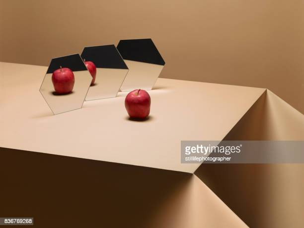 One Apple on table with mirrors