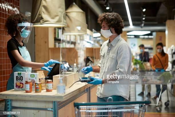 un hombre argentino que paga en la caja - mercado espacio de comercio fotografías e imágenes de stock