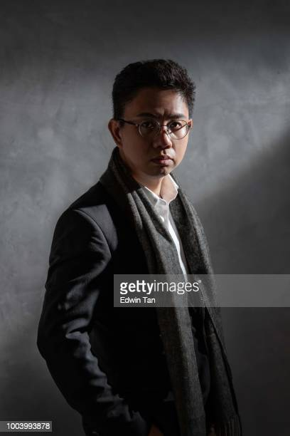 one asian chinese mid adult man looking at camera standing in a studio