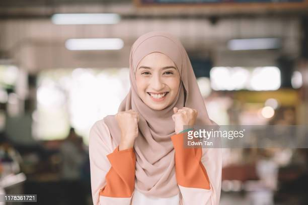one asian muslim female headshot at wet market in the morning outdoor with positive emotion - bella ciao foto e immagini stock