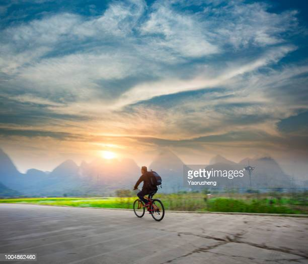 One asian people ride bycycle at Yangshuo moutain area,Yunan,China