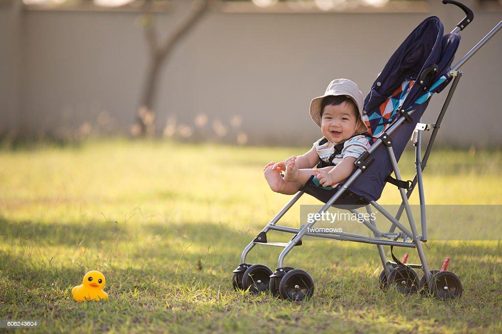 One asian toddler in stroller at garden. : Stock-Foto