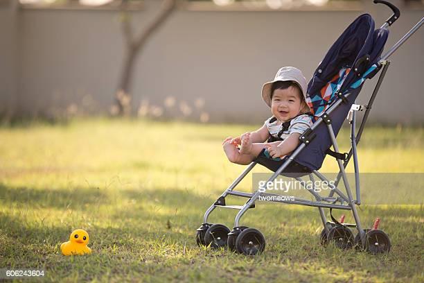 One asian toddler in stroller at garden.
