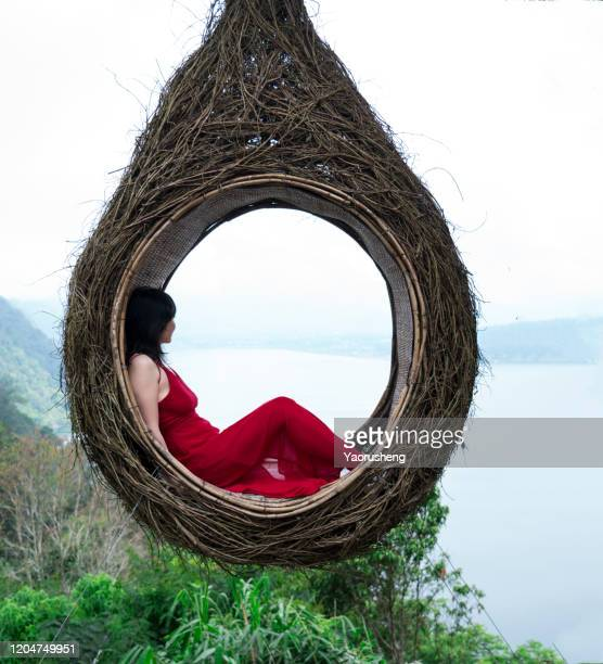 one asian woman in red dress on a man made wooden nest with beautiful nature in the background - red dress stock pictures, royalty-free photos & images
