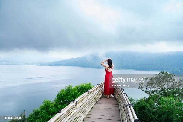 one asian woman in red skirt looking the lake and mountain - aussichtspunkt stock-fotos und bilder