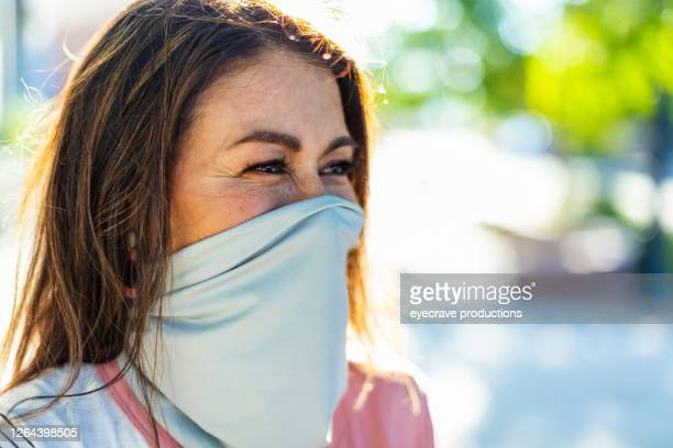 one baby boomer female wearing face mask covering on city street - eyecrave  stock pictures, royalty-free photos & images
