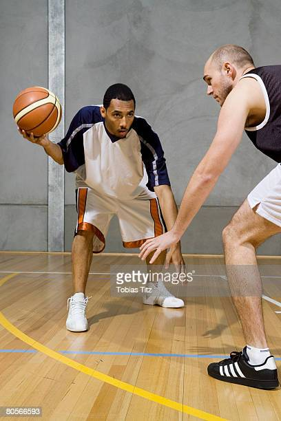 one basketball player dribbles the ball and another player guards him - man bending over from behind stock photos and pictures