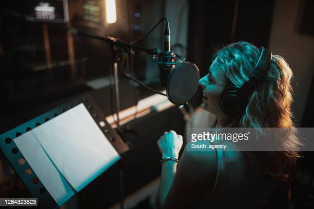 one beautiful female singer recording song in music studio - recording studio stock pictures, royalty-free photos & images