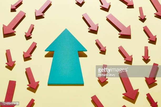 one big arrow moving in the opposite direction to a crowd of small arrows - richard drury stock pictures, royalty-free photos & images