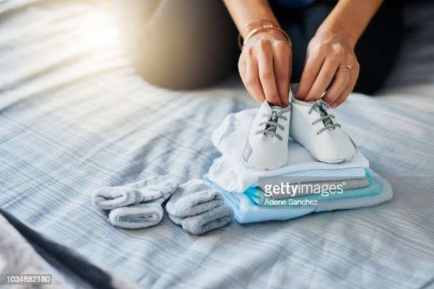 one big blessing will be filling these tiny clothes - baby booties stock photos and pictures