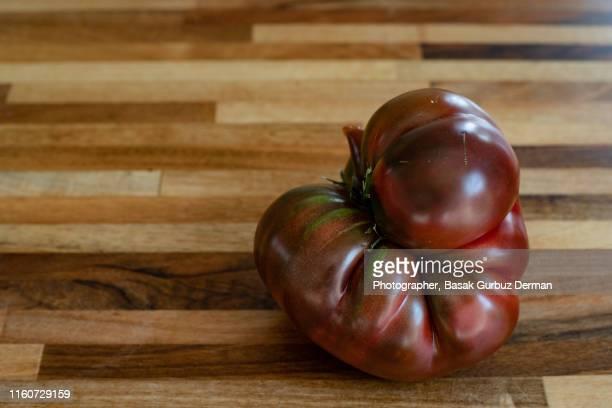 one big organic heirloom tomato - basak gurbuz derman stock photos and pictures