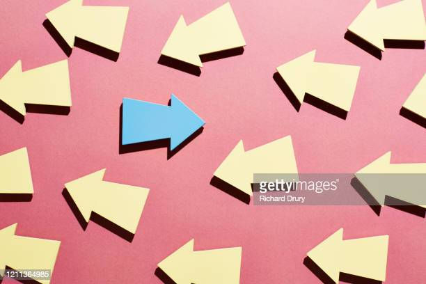one blue arrow moving in the opposite direction to a group of yellow arrows - confrontation stock pictures, royalty-free photos & images