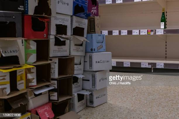 One bottle of Riesling wine is left for sale on emptied shelves next to empty boxes that contained wine at a Sainsburys supermarket as the outbreak...