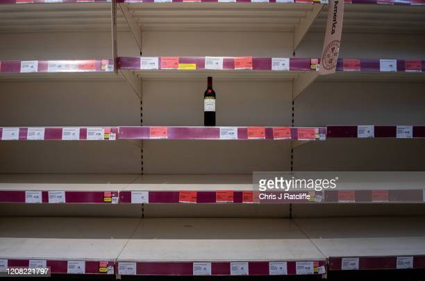 One bottle of shiraz red wine is left for sale on emptied shelves at a Sainsburys supermarket as the outbreak of coronavirus intensifies on March 25,...
