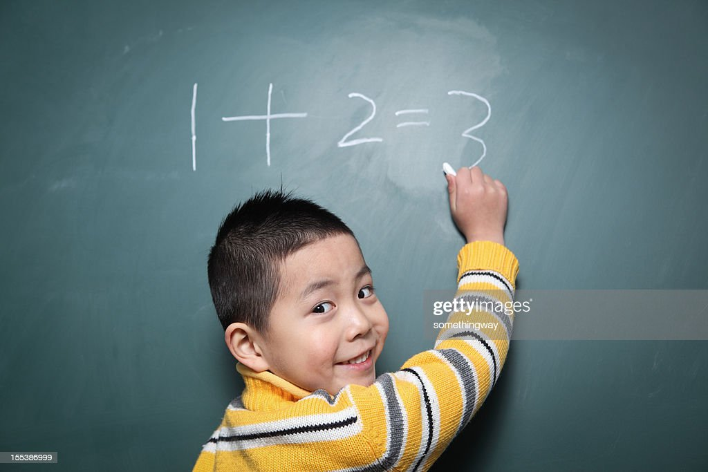 one boy is doing the math question : Stock Photo