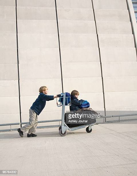 One boy pushing another on luggage trolley